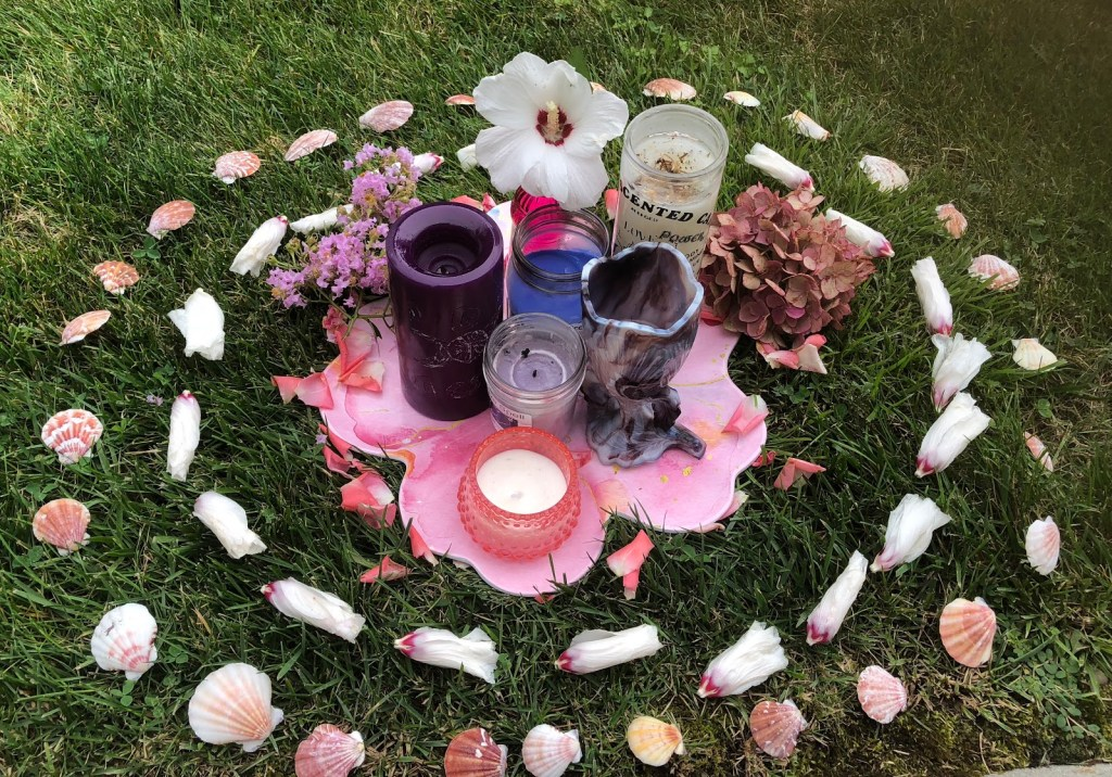 candles, petal, shells in grass for a ritual