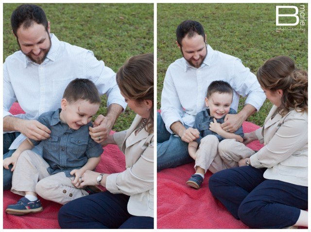 Family portraits tickling son in a park on a red blanket
