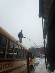 The crew clears snow from the top of the busses.