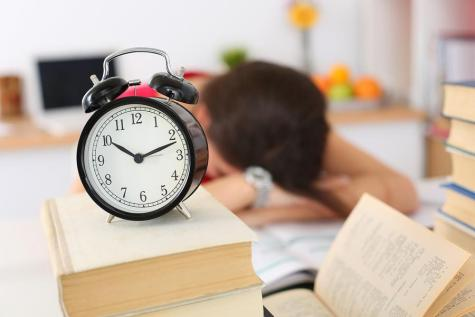 Tired female student at workplace in room taking nap on pile of textbooks. Sleepy brunette woman resting during education after sleepless night. Student in despair caused by exam deadline concept. Photo illustration purchased from BigStock.com.