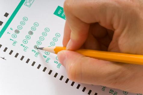 A person wih a yellow pencil taking a multiple choice test or exam