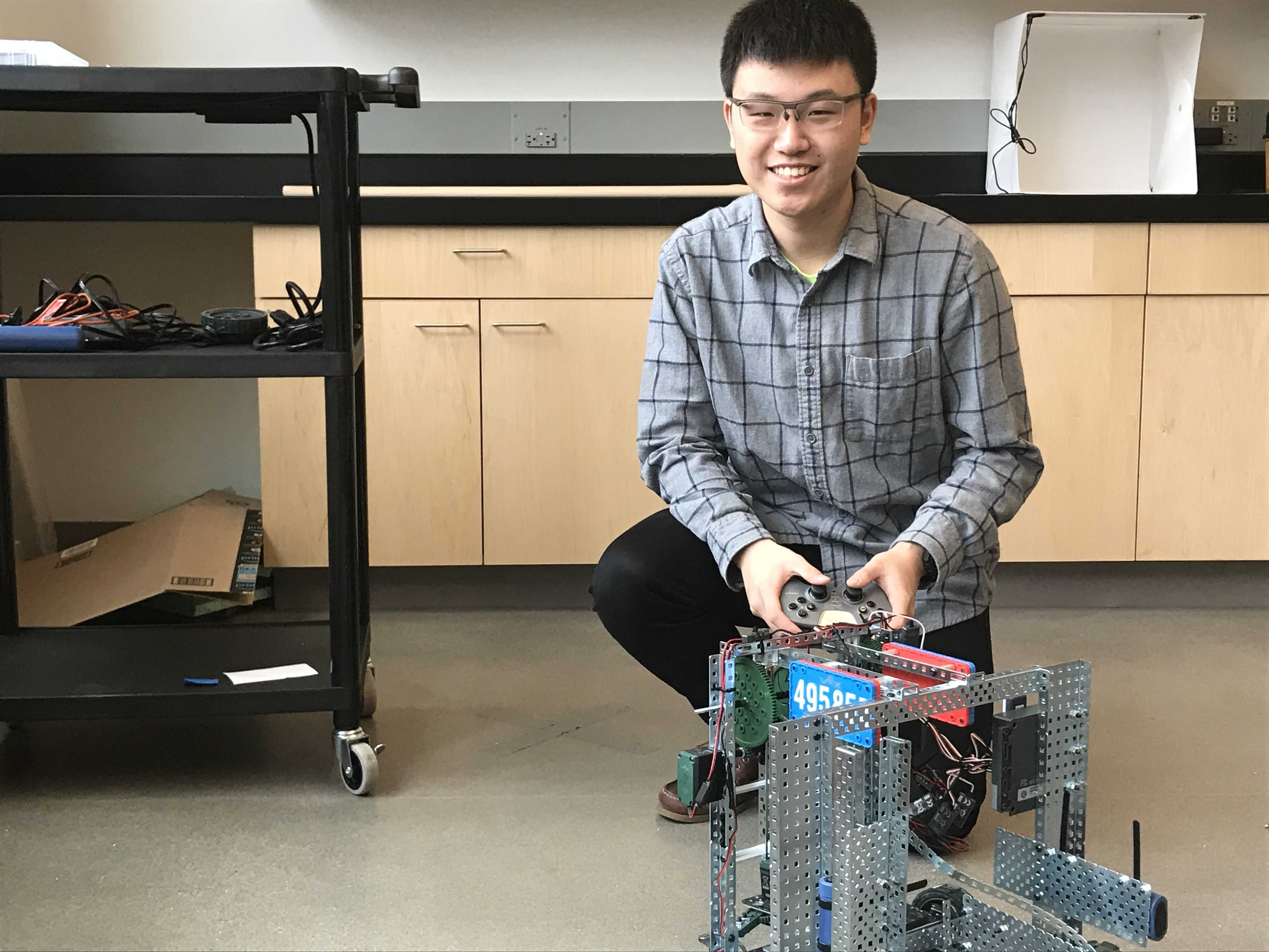 Gator Robotics leader Jeff Wu '18 poses with his machine. Photo by Michael Donahue '18.