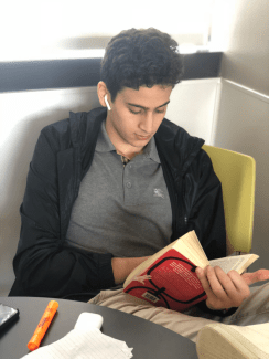 Ahmad Faisal '20 reading a novel for English class. Photo By Sita Alomran '19.