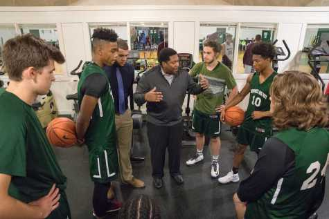 Assistant Athletic Director Tom Nelson, who also teaches math and coaches Varsity 1 basketball, chats with his players at halftime. Photo by David Barron.