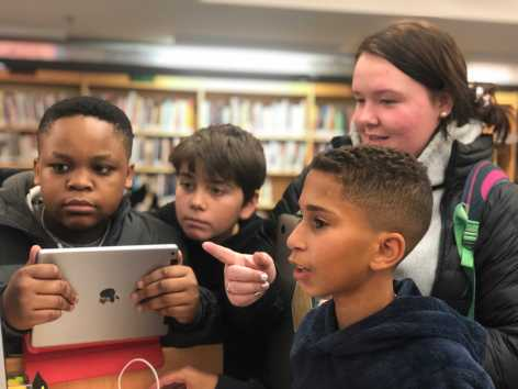 Chloe Cochener '19 helping out Middle school students in the learning commons. Photo By Sita Alomran '19.
