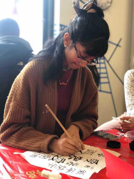 Kusumitha Mallidi '19 working on calligraphy. Photo By Sita Alomran '19.
