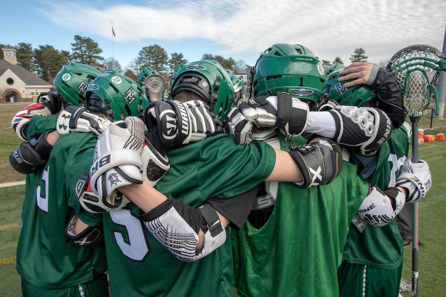 The boys lacrosse team huddles at Mt. Ida. Photo by David Barron.