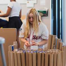 In Kathryn Lee's Problem Solving Through Design elective, Lilliana Palmer '23 assembles a chair made entirely of rolled cardboard.