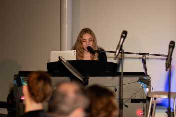 Hannah Liwerant '22 sings a song while playing on the piano.