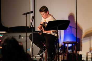 Jude Palmer '22 sings a song while playing on his guitar.