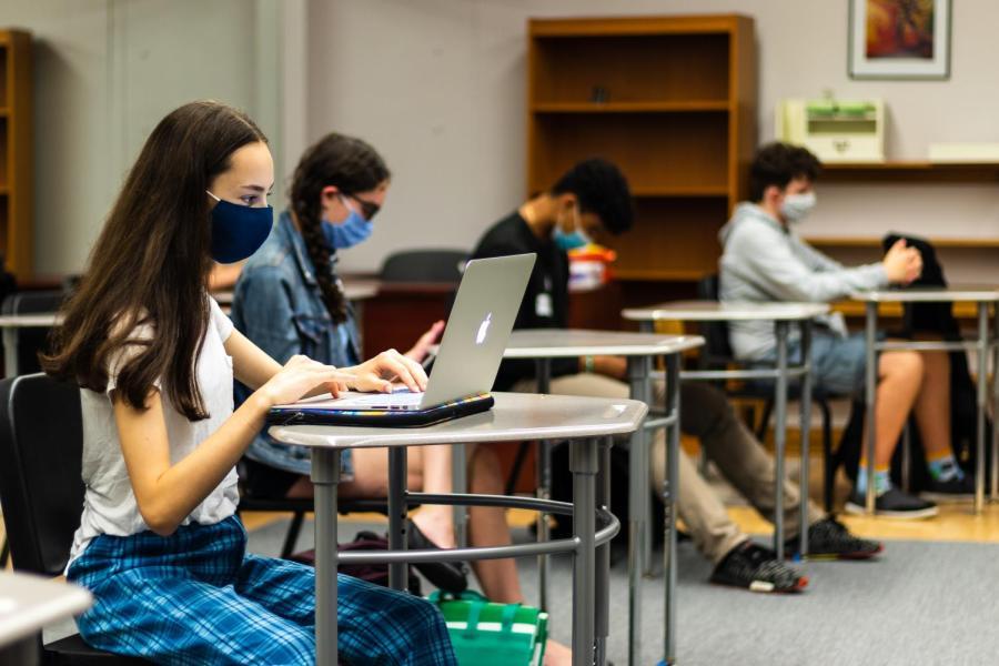 In Upper School classrooms, students sit at desks six feet apart.