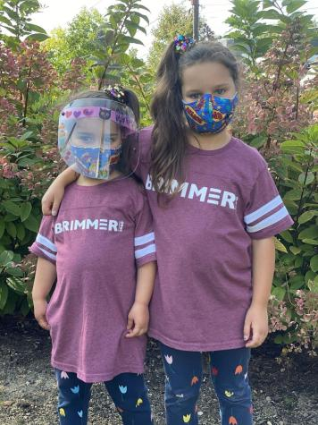 Sister campers pose in masks on campus.