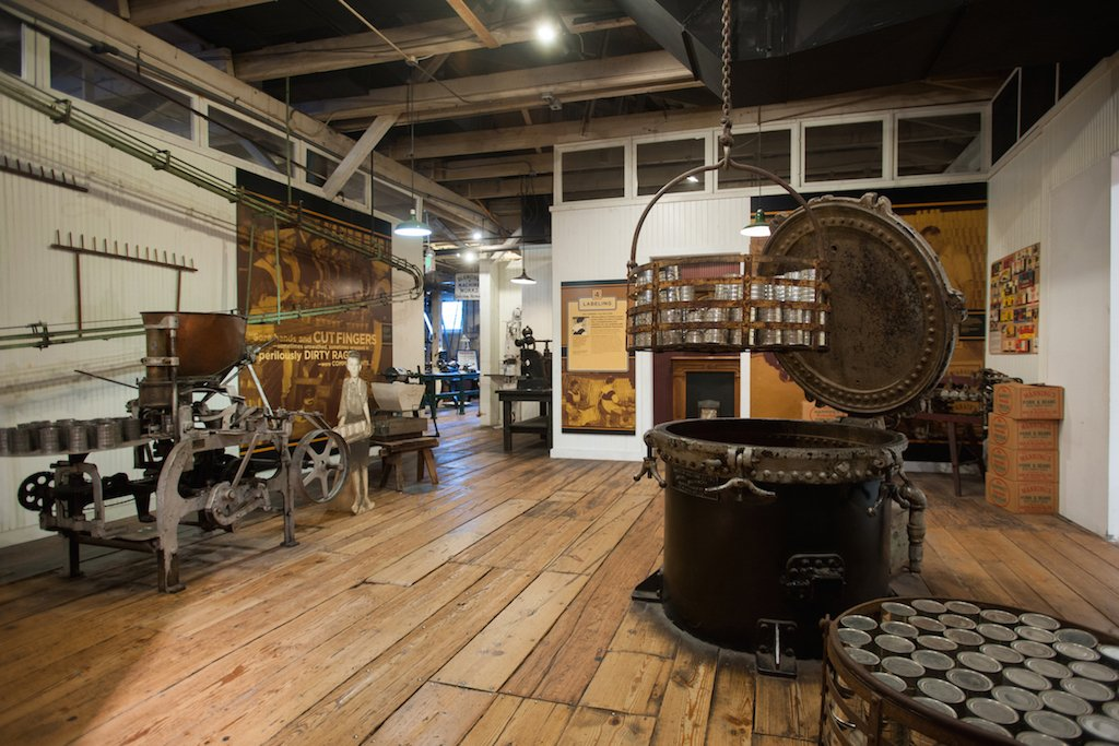 Large space with wood floors with industrial equipment displayed on on the walls and around the room.