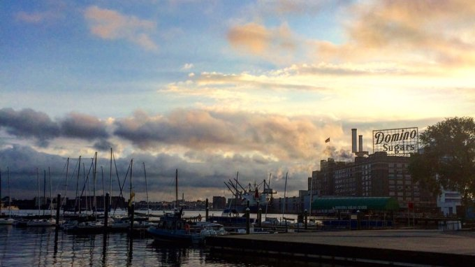 Blue sky with scattered clouds above a pier jutting out into the water. An industrial building with the sign Domino Sugar is in the background.