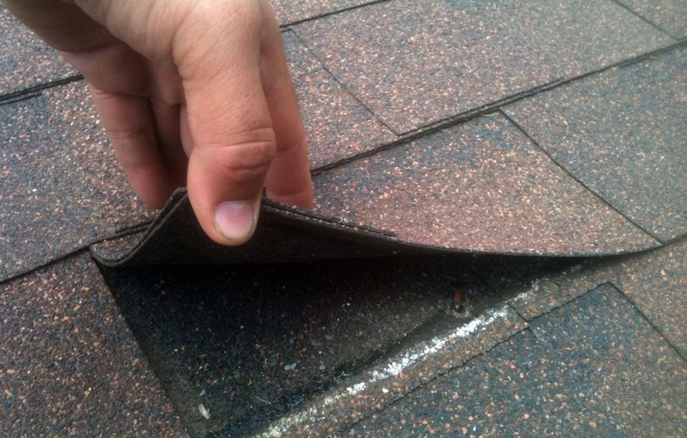 picture of a roofer birmingham doing a roof inspection