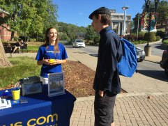 Emily Megna, left, discusses the benefits and prices offered by the Megabus system to Joshua Taylor on Sept. 27, in Morgantown, W. Va. Megna was working the promotions table in front of West Virginia University's Mountain Lair. Photo by Blaithe Tarley.