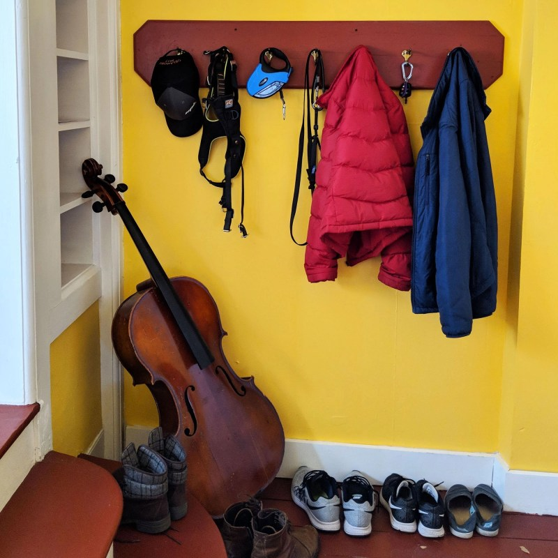 yellow entry way with coat rack and cello