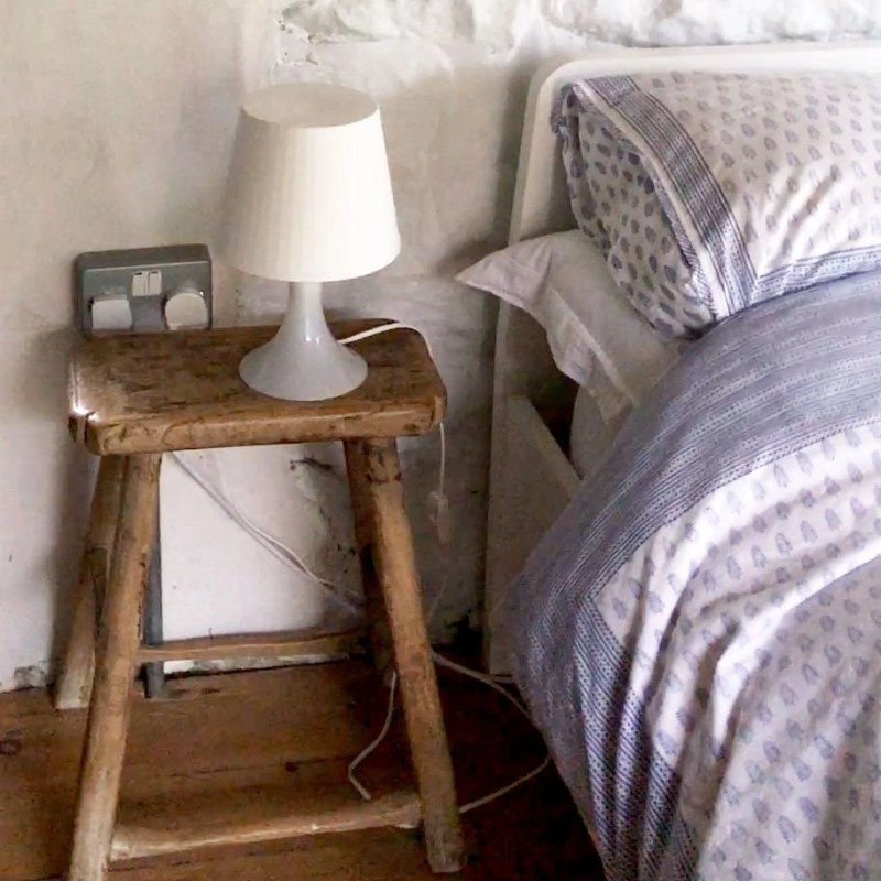 small milkstool serving as a nightstand