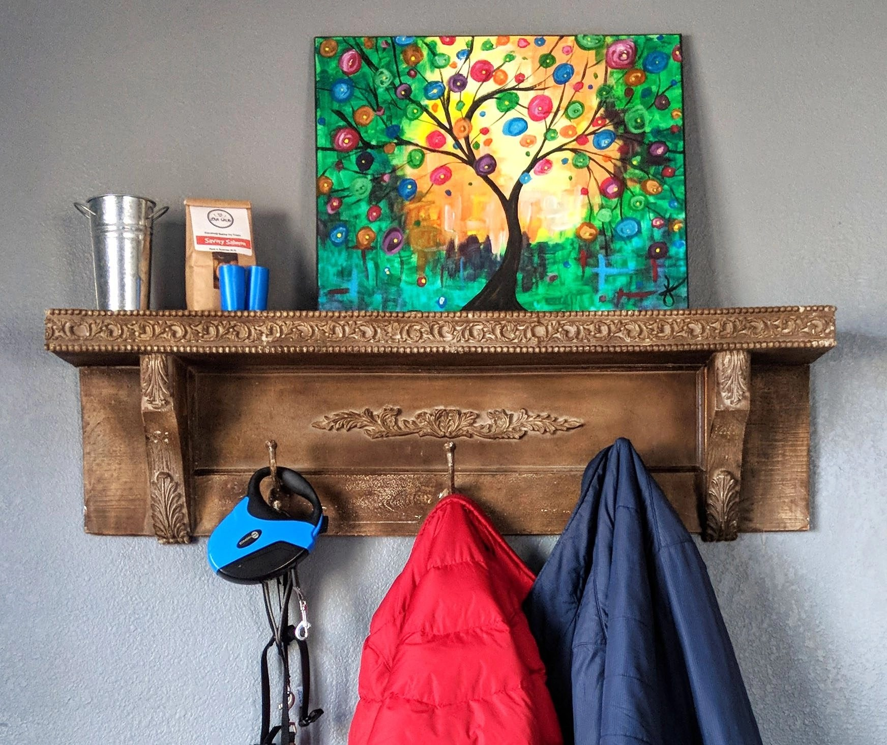 two coats and a dog leash hanging from a wooden coat rack