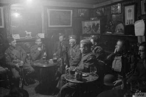 A dimly lit pub with soldiers in discussion.