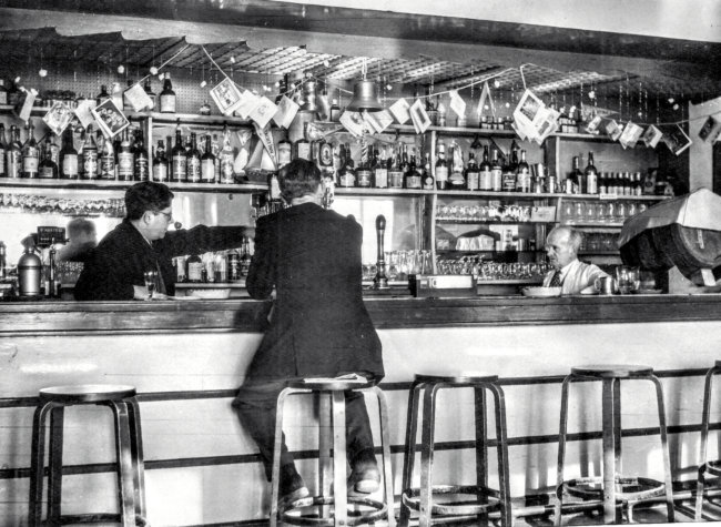 A man in a suit sits at the bar while Frank directs his assistant.