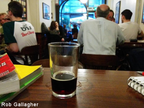 City centre pub with empty beer glass.