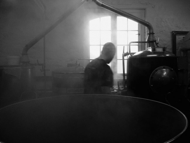 A figure in silhouette surrounded by steam.