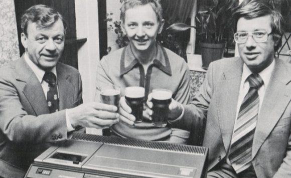 Three men raising pints over a video recorder.