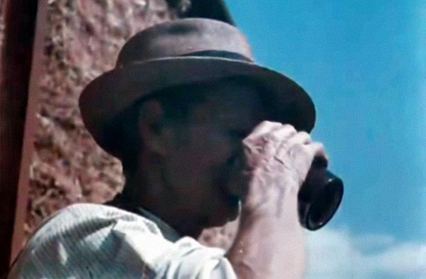 Still from a film: a farmworker drinks homebrew.