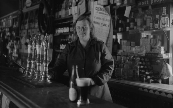 Vintage photo of a woman behind the bar of an Irish pub.