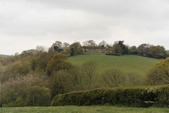 A hillside with farm buildings.