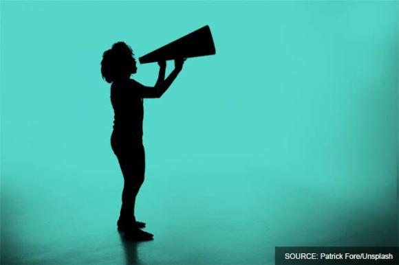 A woman shouting through a loudspeaker