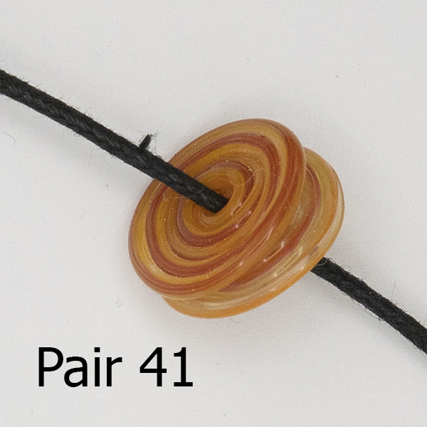 pair of spiral glass discs on a black cor