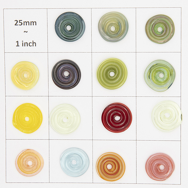 15 glass disc beads sit flat on a 25mm grid to show their sizes. Assorted colours.