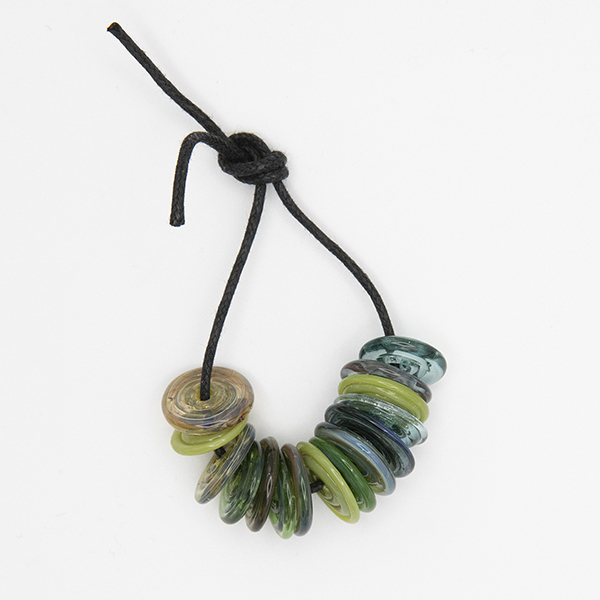 15 borosilicate glass beads, lampword inro spiral siscs. Strung onto a black cord which has been knotted.