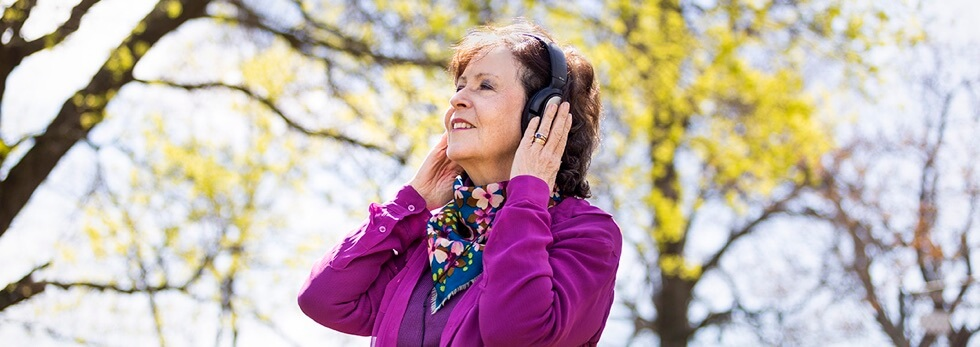 Bobbin Beam Voice Artist listening via headphones in the light with trees in the background