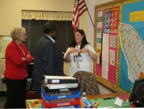 Rogers teacher Julie Underhill leads Ralph Smith on a tour of the school.
