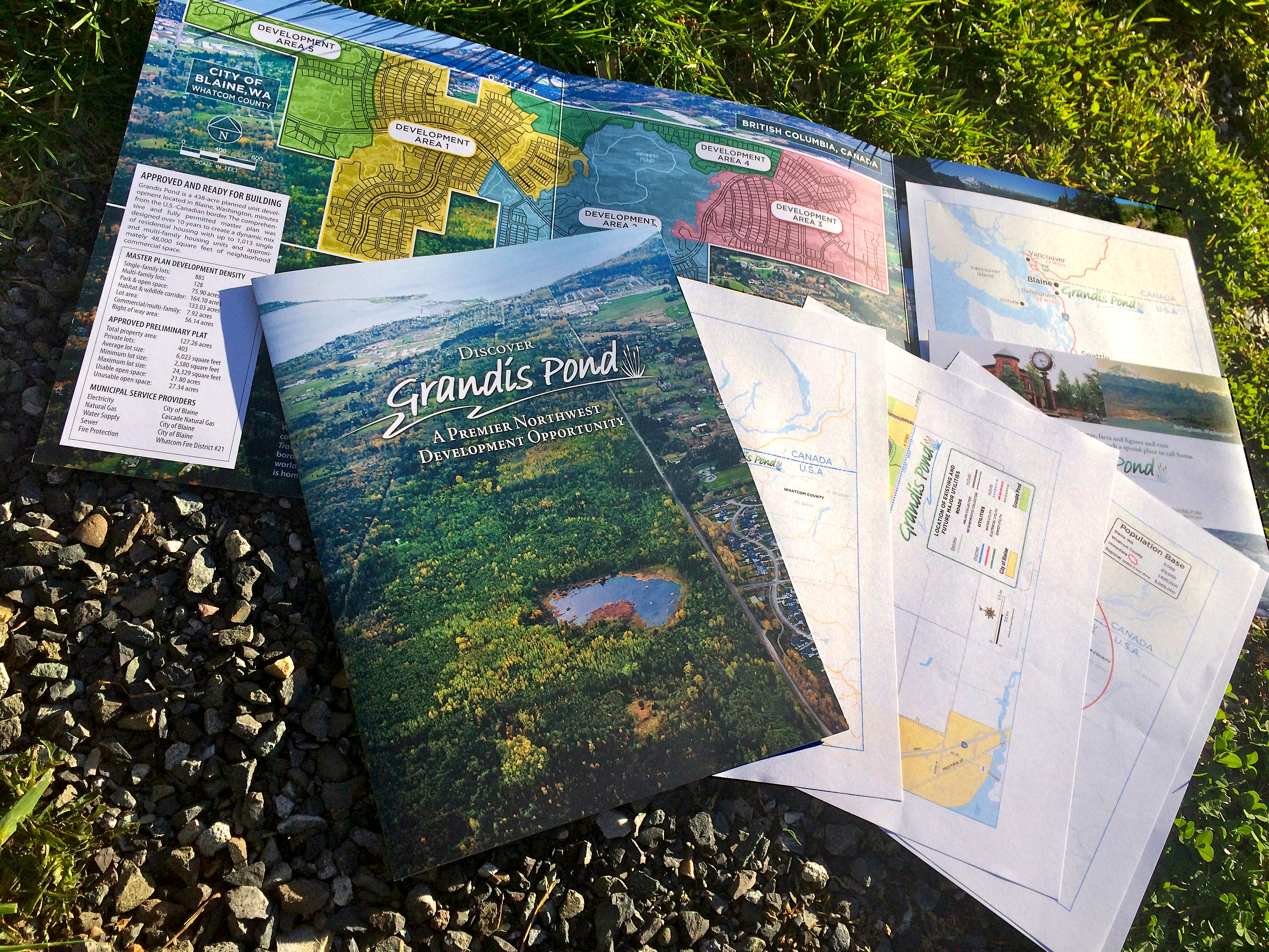 "Grandis Pond 9"" x 12"" (folded) tri-fold brochure with a set of simplified maps that insert int the pocket, showing regional location, population densities, site specifics, and distances to nearby cities in Canada and the stae of Washington."