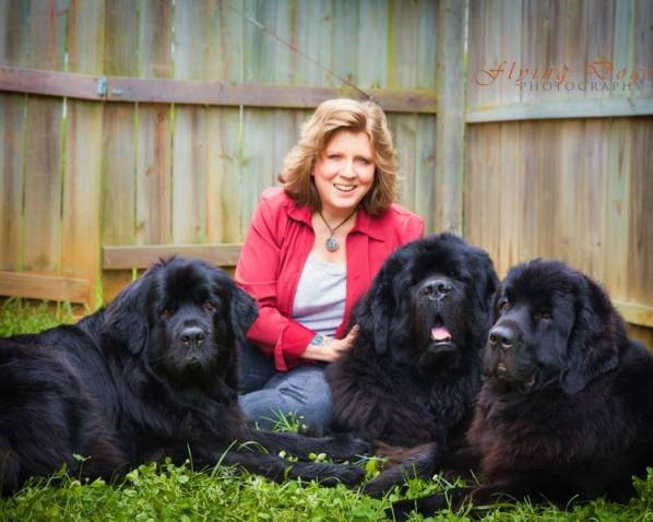 Danielle Bingham in her backyard with her family of Newfoundland dogs