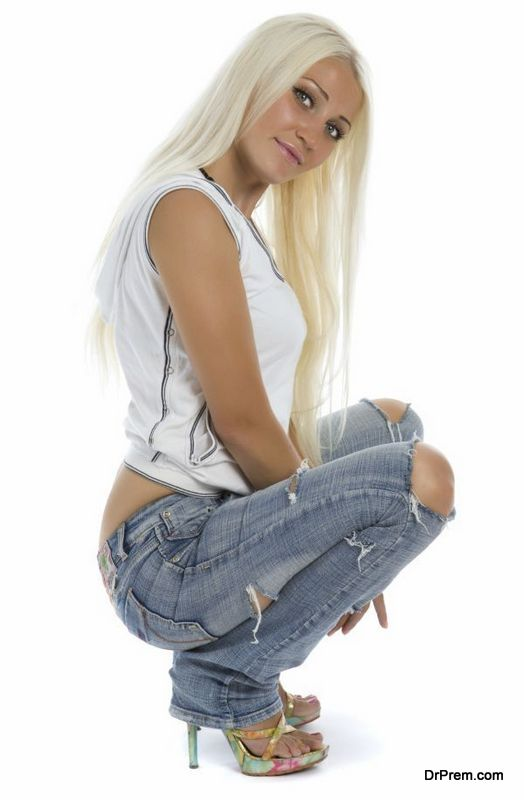 Attractive girl with tattered jeans sit on floor