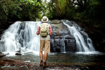 Hiker standing in front of a waterfall deep in the jungle - Sri Lanka