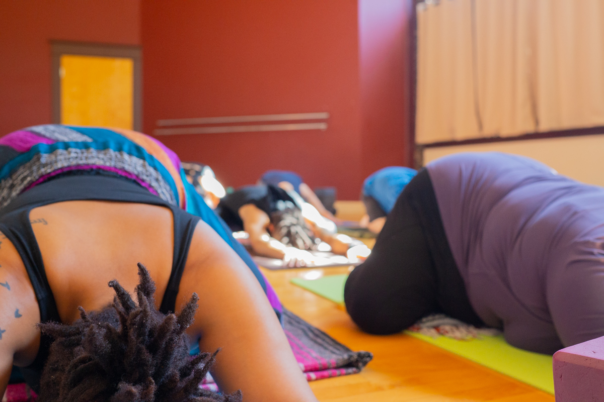 A set of photos depicting a yoga class full of students in a studio with red and white walls and a wooden floor. The students are in various yoga poses, meditating and being assisted by an instructor