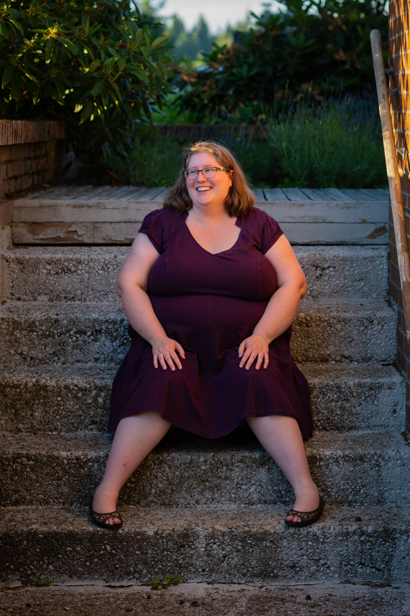 A fat white woman celebrating her 20th wedding anniversary sits on a set of gray steps, wearing glasses and a purple dress.