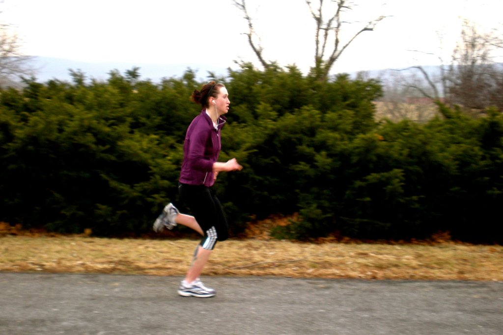 An image of Genevieve, a tall, white, slender girl running down a road. She is wearing running shoes, black capri pants, and a purple sweatshirt. She has headphones in her ears and a determined look on her face.