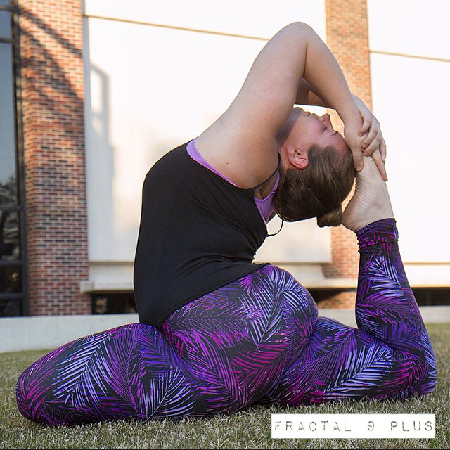 Dana is in one-legged king pigeon pose. She reaches back behind her head and grabs her foot, which is touching her head. She is white with brown hair and dressed in purple patterned leggings and a black tank top.