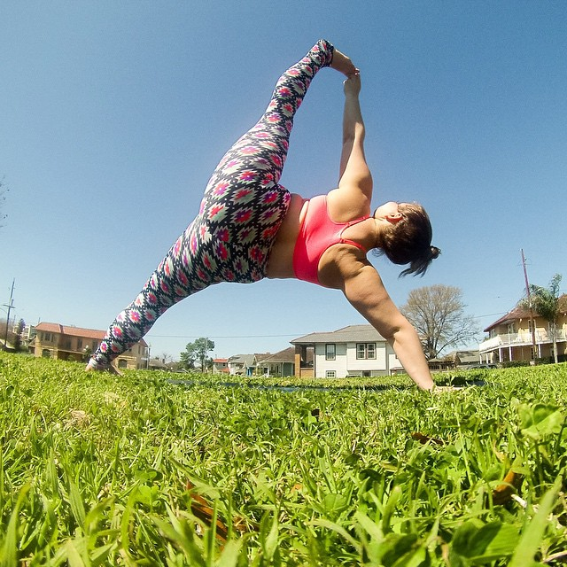 Dana is in vasisthasana - side plank with a variation where she grabs the toes of her top foot. She is dressed in brightly patterned leggings and a pink sports bra.