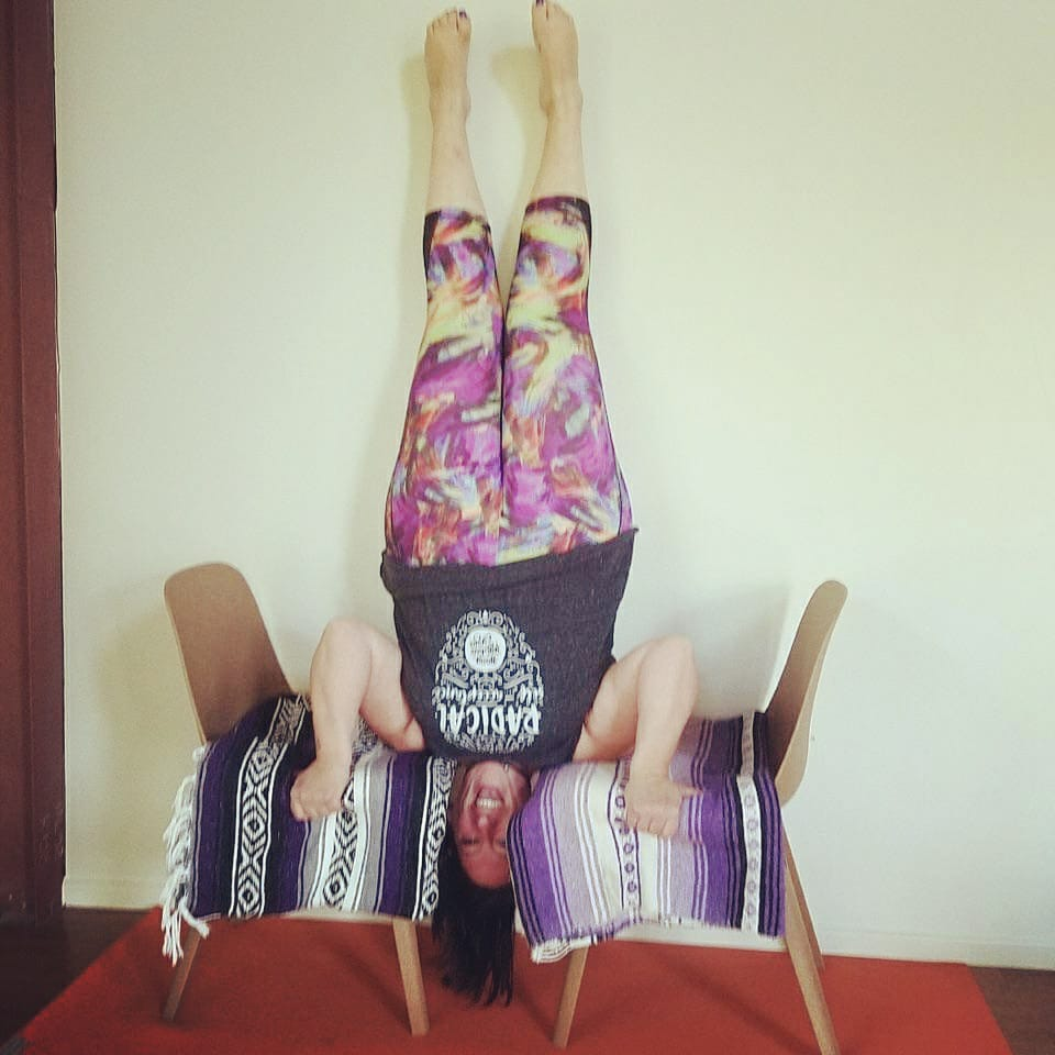 Deb doing headless headstand using 2 chairs - Body Positive Yoga