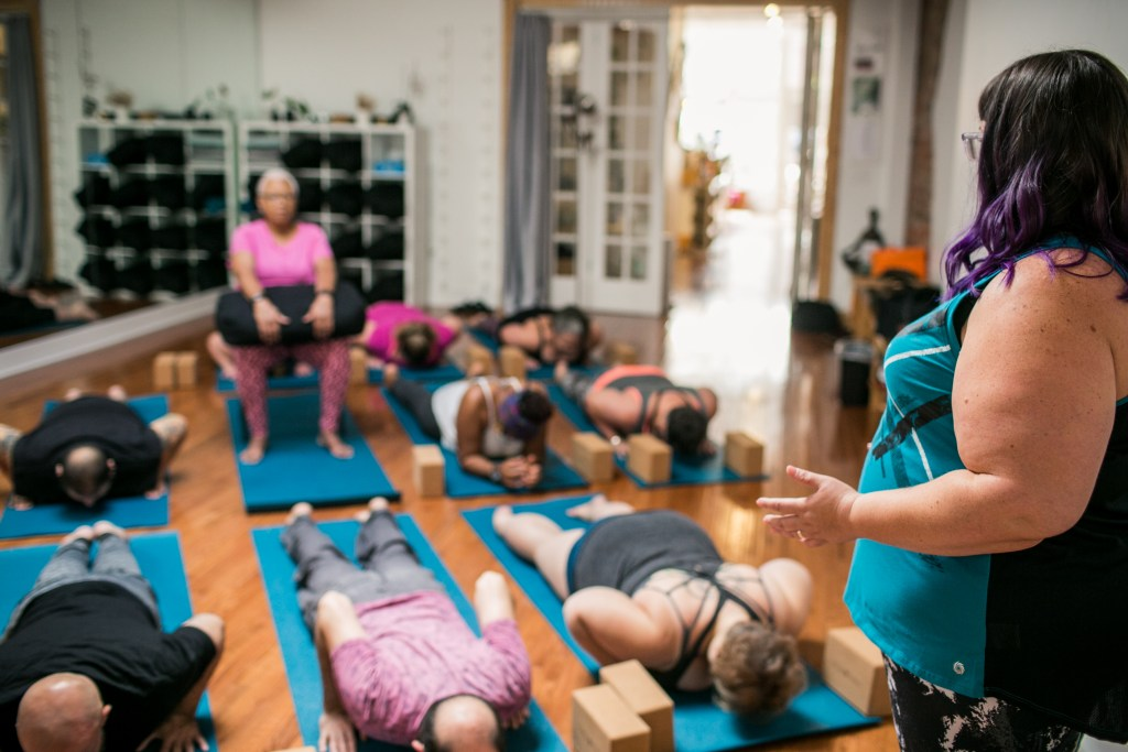 Photograph of Amber standing with her side facing the camera, teaching cobra pose to a diverse class of students. One student is practicing in a chair and the rest are on yoga mats