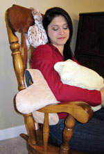 Mother holding baby in rocking chair while using Bone pillows for neck, arm, and shoulder support
