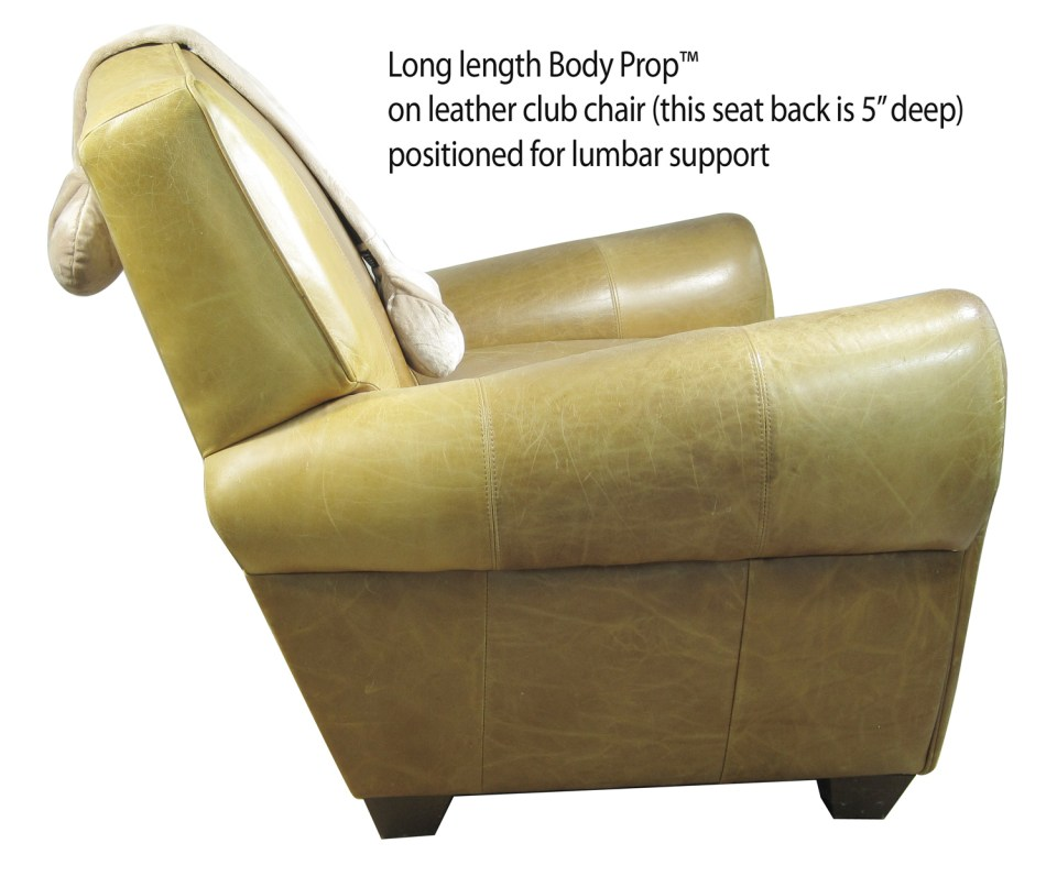 Backbone pillow in color SAND (aka Body Prop Long), draped over a leather club chair, positioned to support the lumbar or back.
